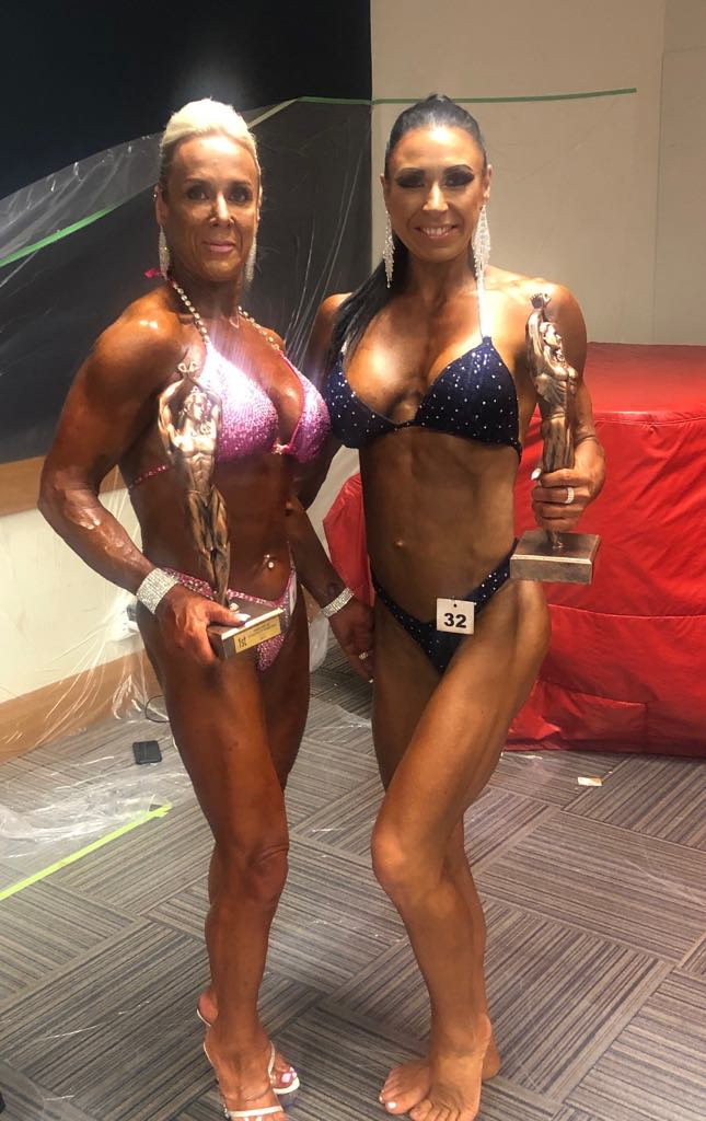 women bodybuilder champions holding their trophies